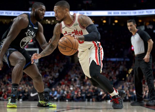 Portland Trail Blazers guard Damian Lillard, right, dribbles past Golden State Warriors forward Eric Paschall during the first half of an NBA basketball game in Portland, Ore., Wednesday, Dec. 18, 2019. (AP Photo/Craig Mitchelldyer)
