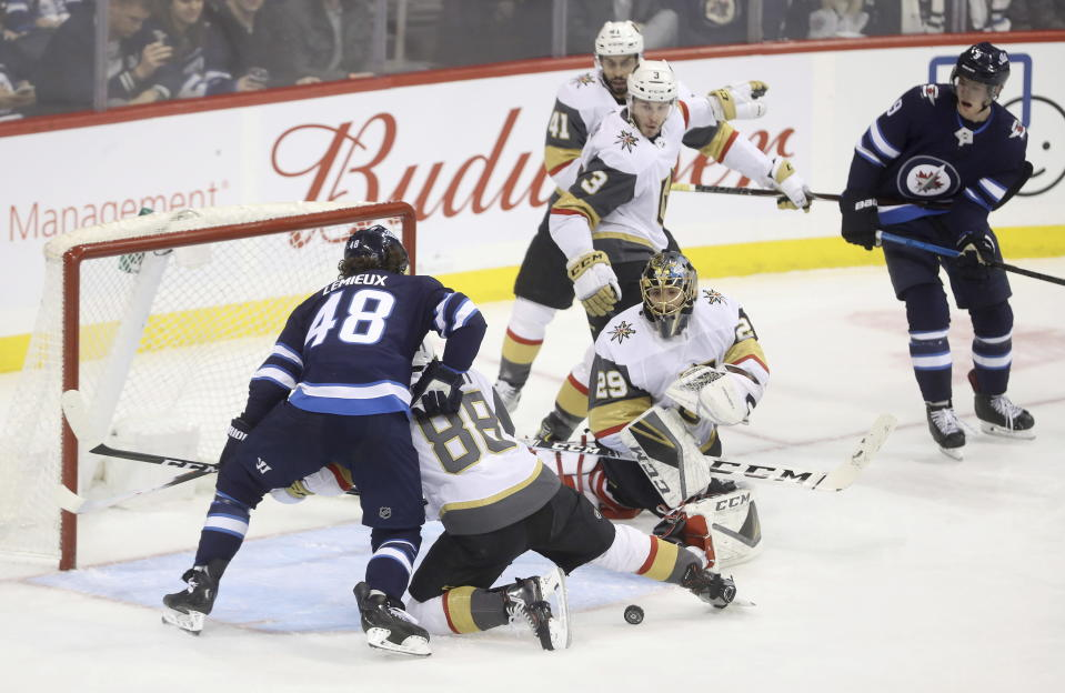 Winnipeg Jets' Brendan Lemieux (48) battles with Vegas Golden Knights' Nate Schmidt (88) in front of Golden Knights goaltender Marc-Andre Fleury (29) during the first period of an NHL hockey game Tuesday, Jan. 15, 2019, in Winnipeg, Manitoba. (Trevor Hagan/The Canadian Press via AP)