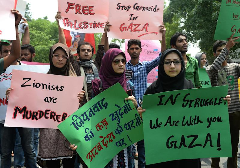 Indian protestors hold placards as they take part in a rally in New Delhi on July 13, 2014 against Israeli attacks on Gaza