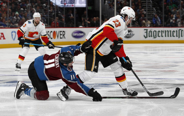 Colorado Avalanche left wing Matt Calvert, front left, blocks Calgary Flames center Sean Monahan who drives to the net in the second period of Game 3 of a first-round NHL hockey playoff series Monday, April 15, 2019, in Denver. (AP Photo/David Zalubowski)