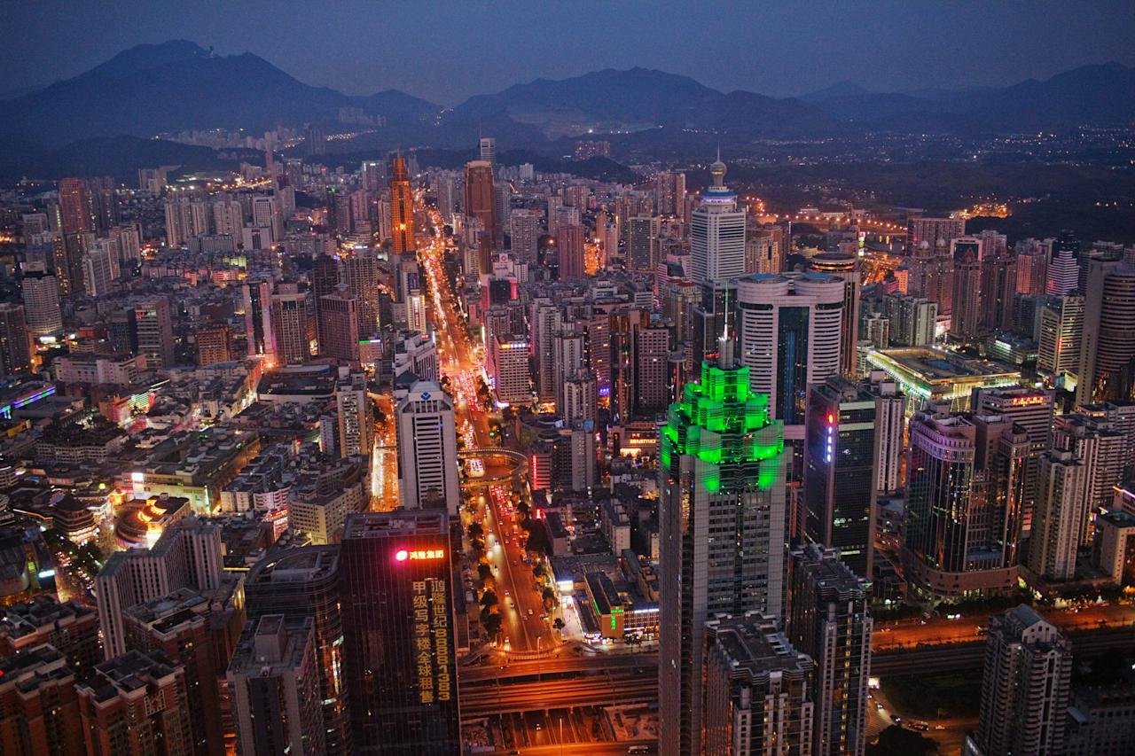 SHENZHEN, CHINA - NOVEMBER 28: The Shenzhen skyline, including The Shenzhen World Financial Center, illuminated by green lights, stretches in to the distance on November 28, 2010 in Shenzhen, China. According to the US Commercial Service, Shenzhen is one of the fastest growing cities in the world. Home of the Shenzhen Stock Exchange and the headquarters of numerous technology companies, the now bustling former fishing village is considered southern China's major financial centre.  (Photo by Daniel Berehulak/Getty Images)