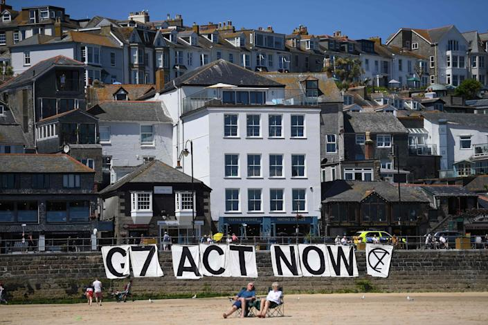 Extinction Rebellion environmental activists attach a banner calling on G7 leaders to act on climate change on the beach in St Ives, Cornwall during the G7 summit on June 13, 202 (AFP via Getty Images)
