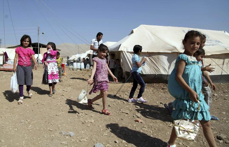 Syrian refugee children play outside a tent during the first day of the Muslim festival of Eid-al-Adha at the Arbat refugee camp in the northern Iraqi province of Sulaimaniya
