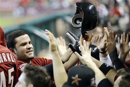 Houston Astros' Jose Altuve, left, is congratulated by teammates after scoring during the seventh inning of a baseball game against the Philadelphia Phillies Sunday, Sept. 16, 2012, in Houston. (AP Photo/David J. Phillip)