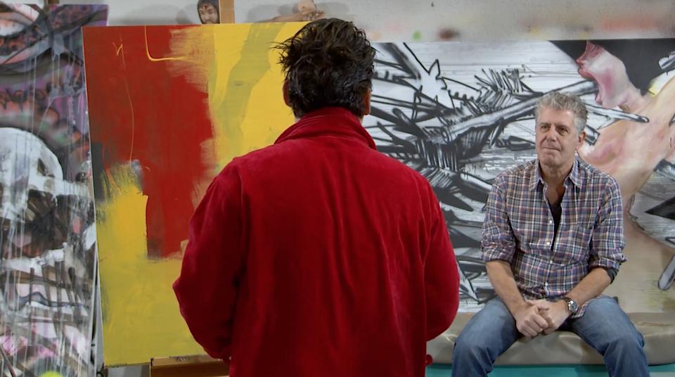 Artist David Choe painting a portrait of Bourdain, who sits across the room from him