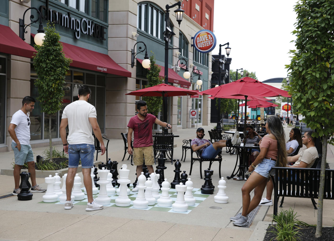 IMAGE DISTRIBUTED FOR WASHINGTON PRIME GROUP - A group of friends from Columbus gather around the giant chess board during the grand opening of The Yard at Polaris Fashion Place Sunday, July 15, 2018 in Columbus, Ohio. The Yard is Polaris Fashion Place's newest community gathering place where people can enjoy outdoor games while shopping and dining. (Jay LaPrete/AP Images for Washington Prime Group)