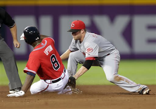 Atlanta Braves' Justin Upton (8) is tagged out by Cincinnati Reds shortstop Zack Cozart, right, while trying to stretch a single in the fourth inning of a baseball game on Friday, July 12, 2013, in Atlanta. (AP Photo/John Bazemore)