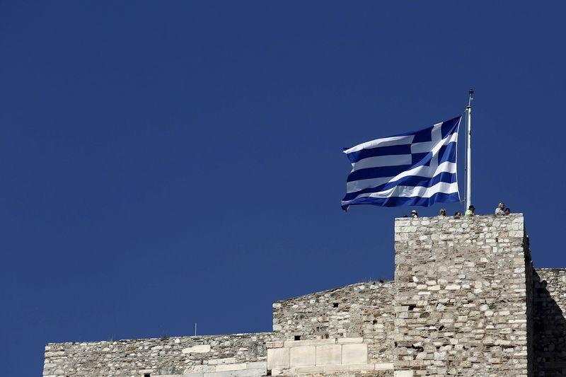 Tourists stand under a Greek national flag atop the Acropolis hill in Athens