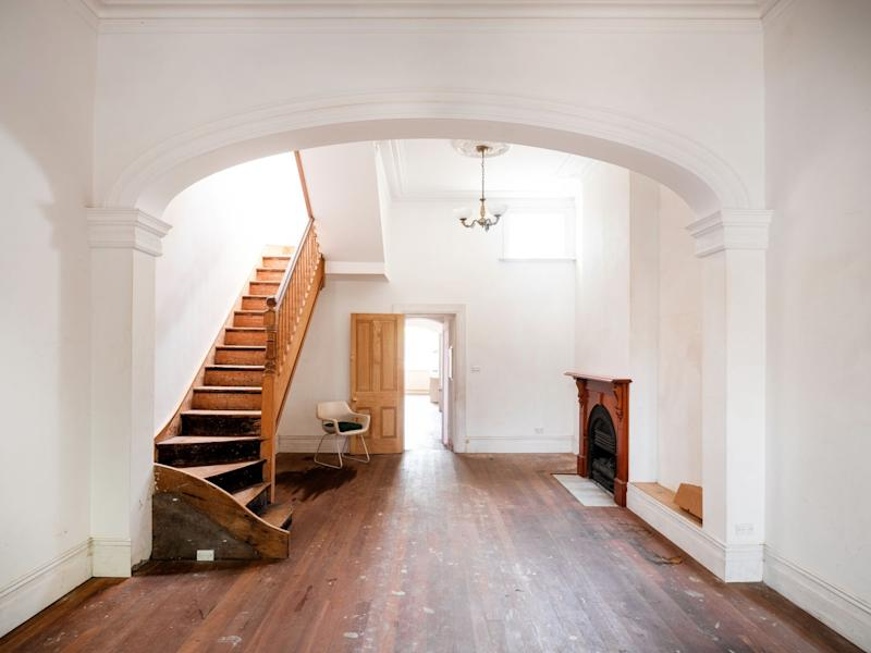 Pictured here is a shot looking into the house (448 Bourke St Sydney) from the front door. Wooden staircase and fireplace are visible Source: Domain