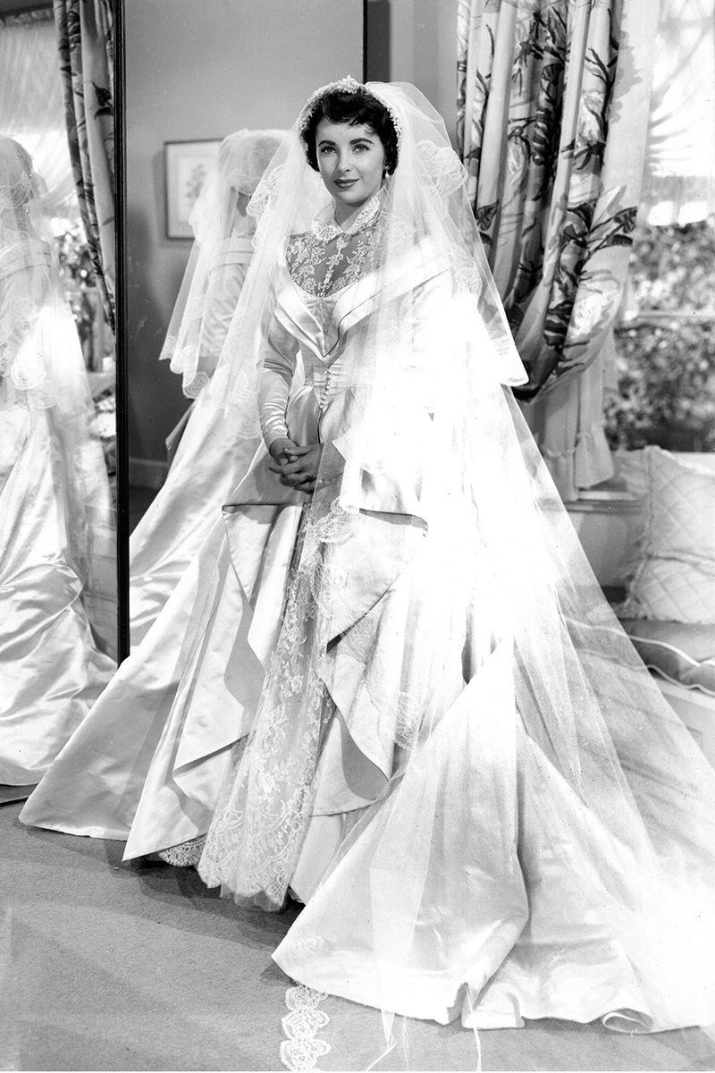 <p>Elizabeth Taylor was a vision in satin and lace for Kay Banks's wedding in <em>Father of the Bride</em>. The actress, who's first wedding to Conrad Hilton coordinated with the release of the film, wore a Helen Rose design for both the film <em>and </em>her real-life nuptials.</p>