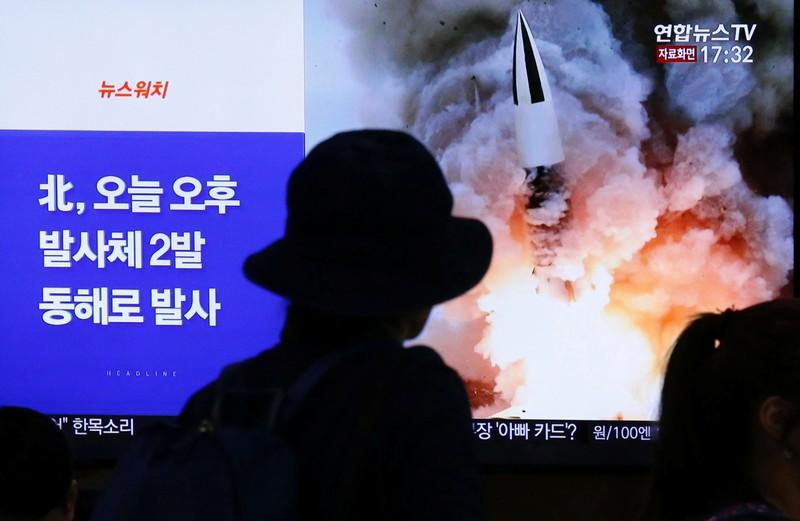 People watch a TV broadcast showing a file footage for a news report on North Korea firing two projectiles, possibly missiles, into the sea, in Seoul