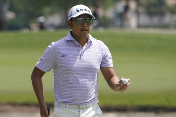 C.T. Pan of Taiwan shows his ball on the first hole during the final round of the Honda Classic golf tournament, Sunday, March 21, 2021, in Palm Beach Gardens, Fla. (AP Photo/Marta Lavandier)
