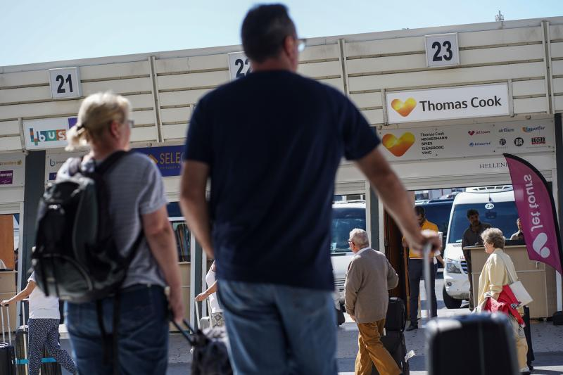 Tourists stand by a counter of Thomas Cook at Heraklion airport on the island of Crete after the travel group collapsed