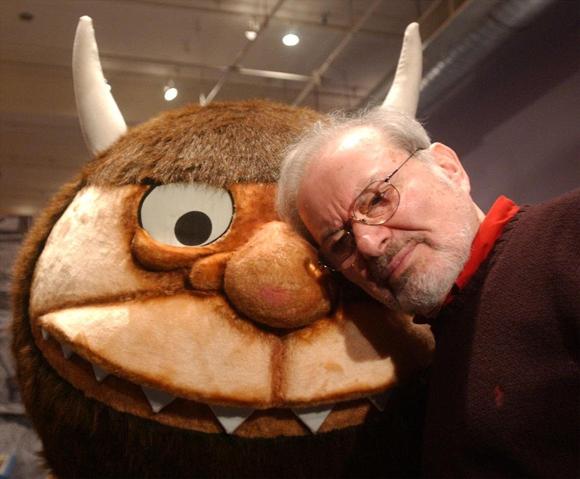 "Standing with a character from his book ""Where the Wild Things Are,"" author and illustrator Maurice Sendak speaks with the media January 11, 2002 before the opening of an exhibition entitled, ""Maurice Sendak In His Own Words and Pictures,"" at the Childrens Museum of Manhattan in New York City. The multimedia exhibition, which opens January 12, will feature photographs, text, illustrations, music and audiovisual components. (Photo by Spencer Platt/Getty Images)"