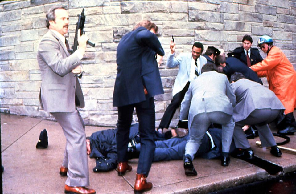 Secret Service agents with guns drawn swarm around Thomas Delahanty and James Brady, both in prone position, while apprehending shooting suspect John Hinckley Jr.