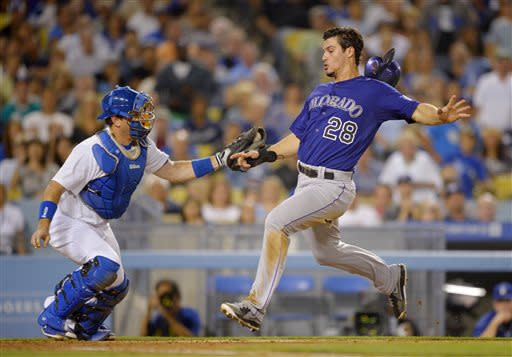 Colorado Rockies' Nolan Arenado, right, scores under the tag of Los Angeles Dodgers catcher A.J. Ellis on a single by DJ LeMahieu during the fifth inning of their baseball game, Friday, July 12, 2013, in Los Angeles. (AP Photo/Mark J. Terrill)