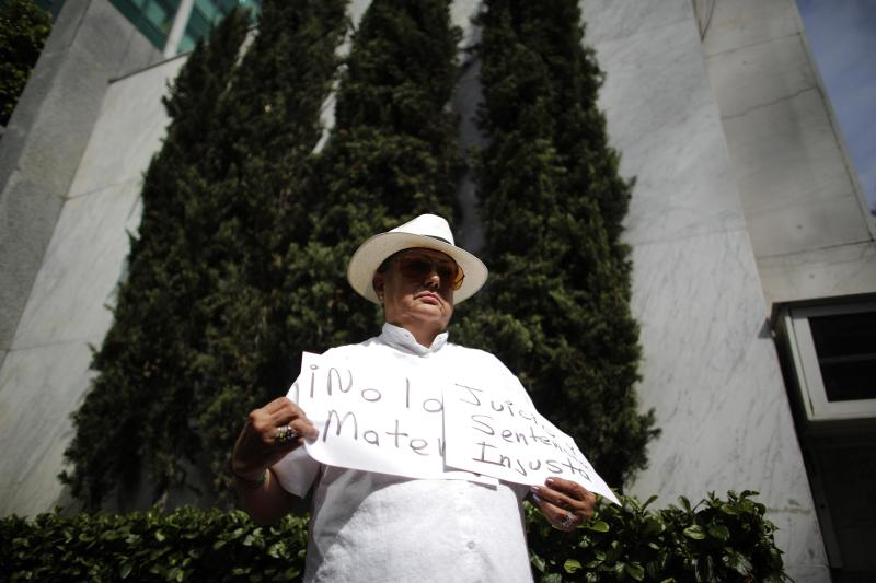 "A member of the bi-national migrant organisation Aztlan holds paper sheets reading ""Don't kill him. Judge and sentence unfair"" during a protest outside the Texas offices in Mexico City"