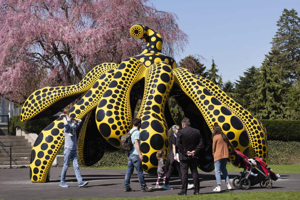 A family walks by one of Yayoi Kusama's pumpkin sculptures at the New York Botanical Garden, Thursday, April 8, 2021 in New York. The expansive exhibit has opened, and ticket sales have been brisk in a pandemic-weary city hungry for more outdoor cultural events. (AP Photo/Mark Lennihan)