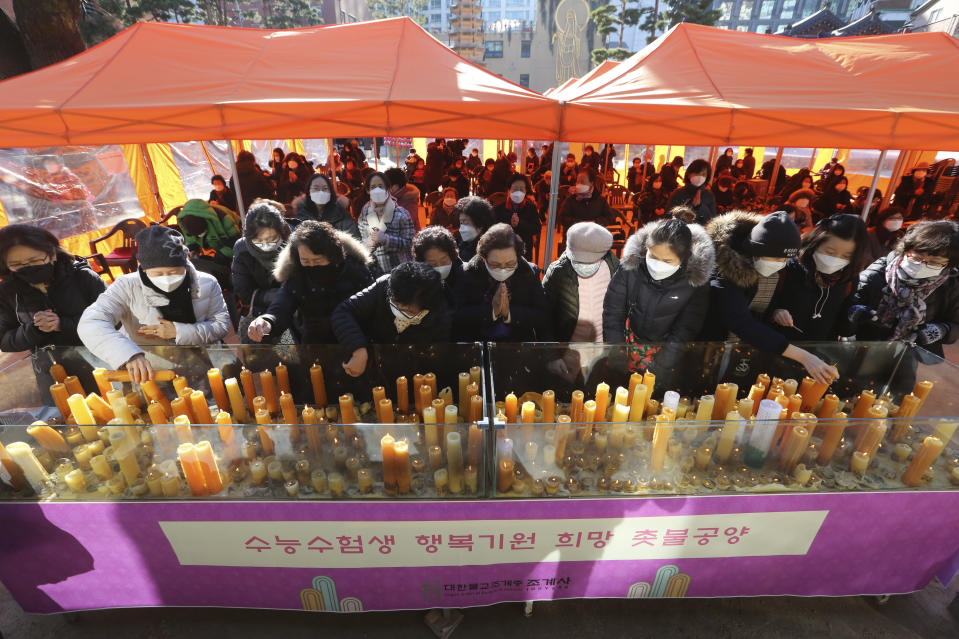 Parents place candles during a special service to wish for their children's success in the college entrance exams at the Jogyesa Buddhist temple in Seoul, South Korea, Thursday, Dec. 3, 2020. Hundreds of thousands of masked students in South Korea, including dozens of confirmed COVID-19 patients, took the highly competitive university entrance exam Thursday despite a viral resurgence that forced authorities to toughen social distancing rules. (AP Photo/Ahn Young-joon)