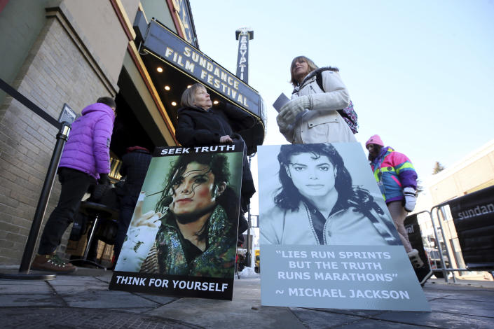 """FILE- In this Jan. 25, 2019, file photo Brenda Jenkyns, left, and Catherine Van Tighem who drove from Calgary, Canada stand with signs outside of the premiere of the """"Leaving Neverland"""" Michael Jackson documentary film at the Egyptian Theatre on Main Street during the 2019 Sundance Film Festival in Park City, Utah. Jackson accusers Wade Robson and James Safechuck say that the Sundance Film Festival is first time they've ever felt public support for their allegations the King of Pop molested them. The documentary which premiered at the festival in January, and will air on HBO in two parts on March 3 and 4, chronicles how their lives intersected with Jackson's. (Photo by Danny Moloshok/Invision/AP, File)"""