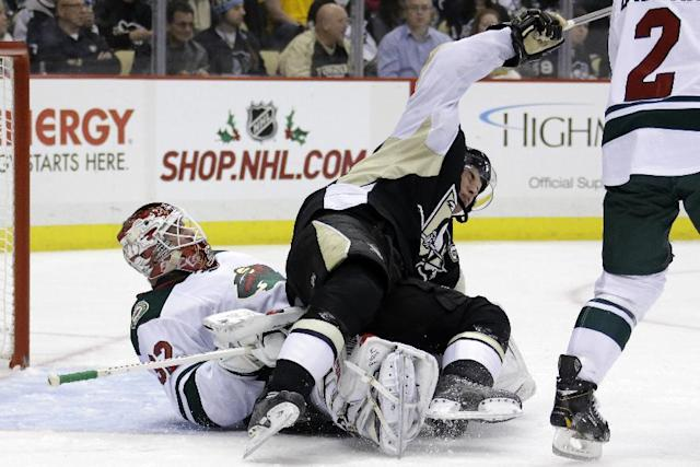 Pittsburgh Penguins' Sidney Crosby, top, collides with Minnesota Wild goalie Niklas Backstrom (32) during the second period of an NHL hockey game in Pittsburgh, Thursday, Dec. 19, 2013. Crosby was penalized for goaltender interference on the play. (AP Photo/Gene J. Puskar)