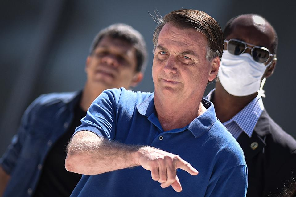 Brazil's President Jair Bolsonaro attends his supporters during a protest in favor of the government and and against the lockdown amid the Coronavirus (COVID-19) outbreak in front of the Planalto Palace in Brasilia, Brazil, on Sunday, May 3, 2020.  Demonstrators asked for military intervention against the Brazil's Federal Supreme Court and the National Congress. With no face mask, Bolsonaro gestured to protesters who were crowding in front of the building. The president came close to the grid and allowed the participants of the act to enter, who went up the ramp and extended a Brazilian flag. (Photo by Andre Borges/NurPhoto via Getty Images)