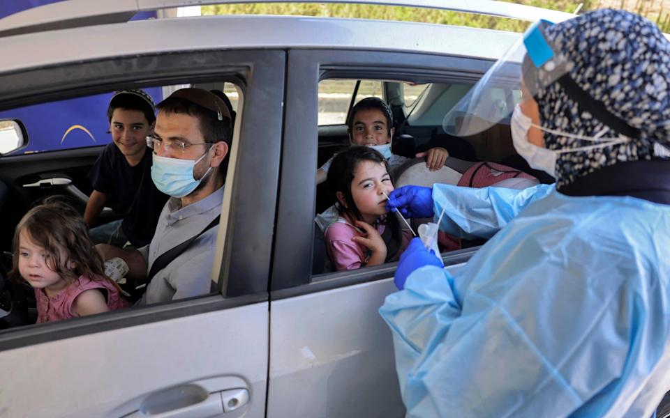 A medical worker performs a Covid-19 test on a child at a drive-through testing centre in Jerusalem, Israel on 29 July 2021 - Menahem Kahana/AFP