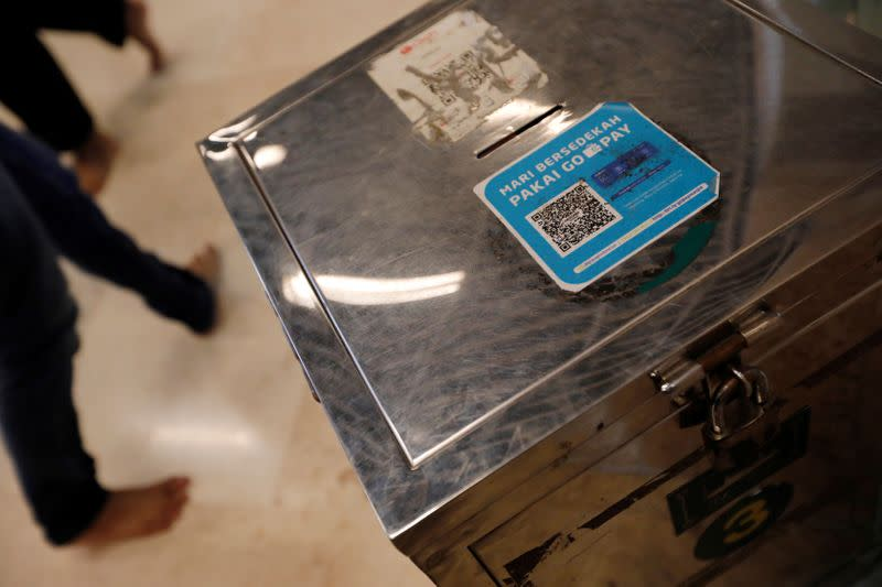 An alms box with a QR code for digital payments is seen after Friday prayers at Istiqlal mosque in Jakarta