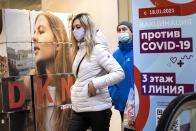 """A woman wearing a face mask to protect against coronavirus walks past a poster reading """"vaccination against COVID-19"""" at the GUM, the State Department store, near Red Square in Moscow, Russia, Wednesday, March 31, 2021. Russia has boasted about being the first country in the world to authorize a coronavirus vaccine and rushed to roll it out earlier than other countries, even as large-scale testing necessary to ensure its safety and effectiveness was still ongoing. (AP Photo/Alexander Zemlianichenko)"""