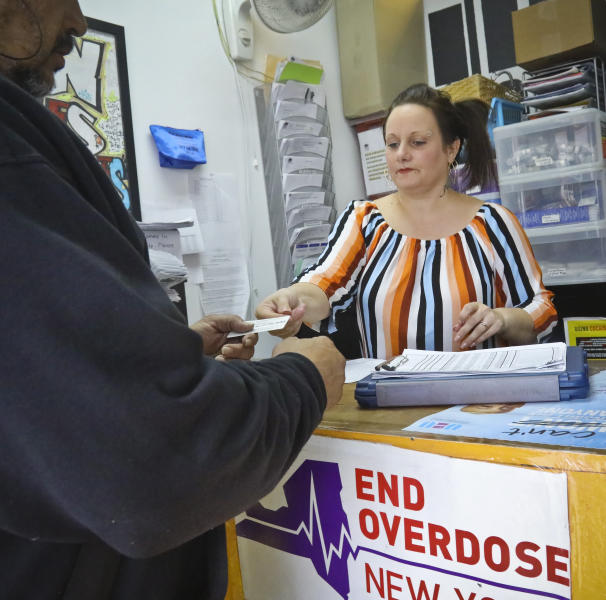 In this Friday, March 15, 2019 photo, Laura Levine prepares to register a new client at Vocal NY, an organization that works with addicts, where she is the health educator and coordinator for the opioid reversal drug Narcan, in the Brooklyn borough of New York. New York state is considering providing medication-assisted treatment to all prison and jail inmates struggling with opioid addiction. (AP Photo/Bebeto Matthews)
