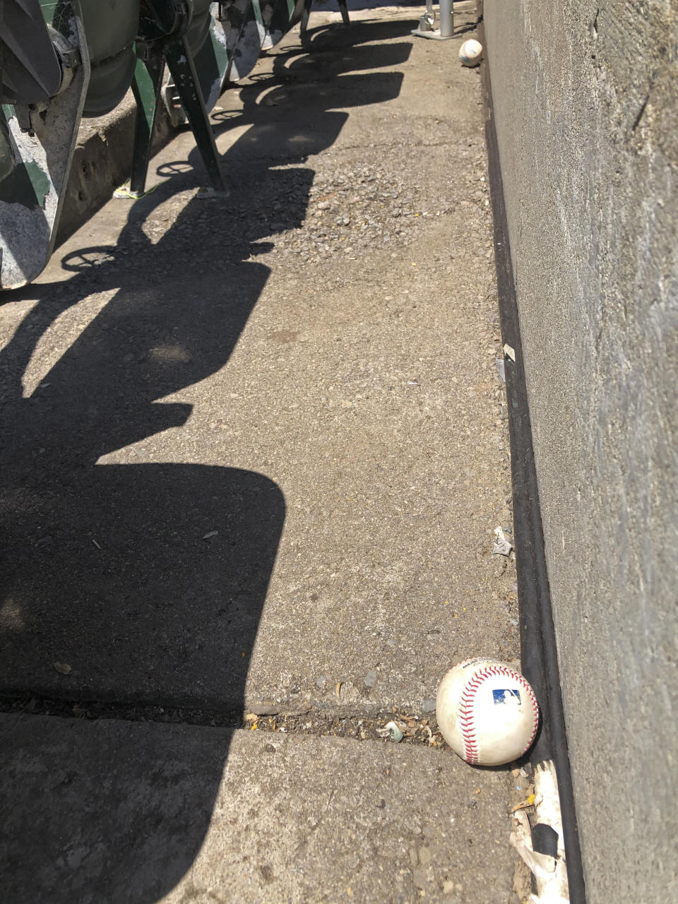 Baseballs fouled off by players are seen stopped at the bottom row of the Oakland Coliseum after rolling down through empty stands during the baseball game between the Los Angeles Angels and the Oakland Athletics on Monday, July 27, 2020, in Oakland, Calif. (AP Photo/Ben Margot)