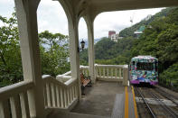 A Peak Tram passes an uphill of the Victoria Peak in Hong Kong on June 17, 2021. Hong Kong's Peak Tram is a fixture in the memories of many residents and tourists, ferrying passengers up Victoria Peak for a bird's eye view of the city's many skyscrapers. (AP Photo/Vincent Yu)