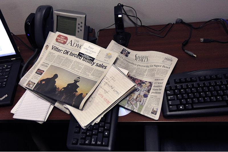 Newspapers, reporters work pads, keyboards and phones are seen on the new Baton Rouge Advocate New Orleans bureau's temporary workspace in New Orleans, Thursday, Sept. 27, 2012. As The Times-Picayune in New Orleans scales back its print edition to three days a week, the Baton Rouge newspaper is starting its own daily edition to try to fill the void. The move by The Advocate sets up an old-fashioned newspaper competition, even as more and more people get their news online and from cellphones. (AP Photo/Gerald Herbert)
