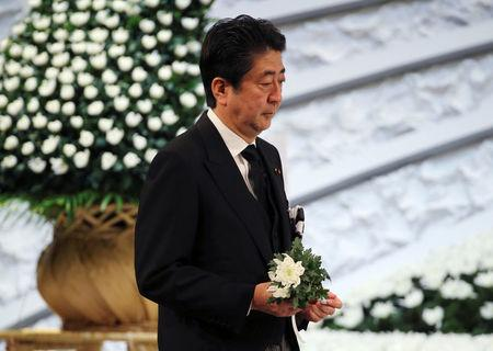 Japanese Prime Minister Shinzo Abe holds a chrysanthemum to offer for the victims of the March 11, 2011 earthquake and tsunami during the national memorial service in Tokyo