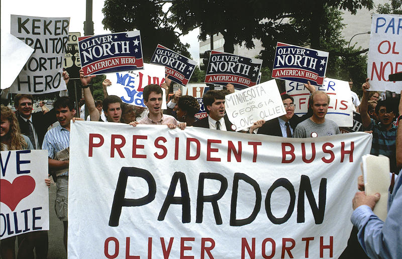 Oliver North became a conservative star after he defiantly admitted to breaking the law in the Iran-Contra scandal. His supporters rallied to his side ahead of his sentencing hearing in 1989. (Mark Reinstein via Getty Images)