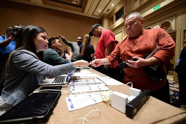 Bellagio Hotel workers show ID as they check in before taking part in the Democratic caucus in Las Vegas, Nevada on February 22, 2020 (AFP Photo/FREDERIC J. BROWN)