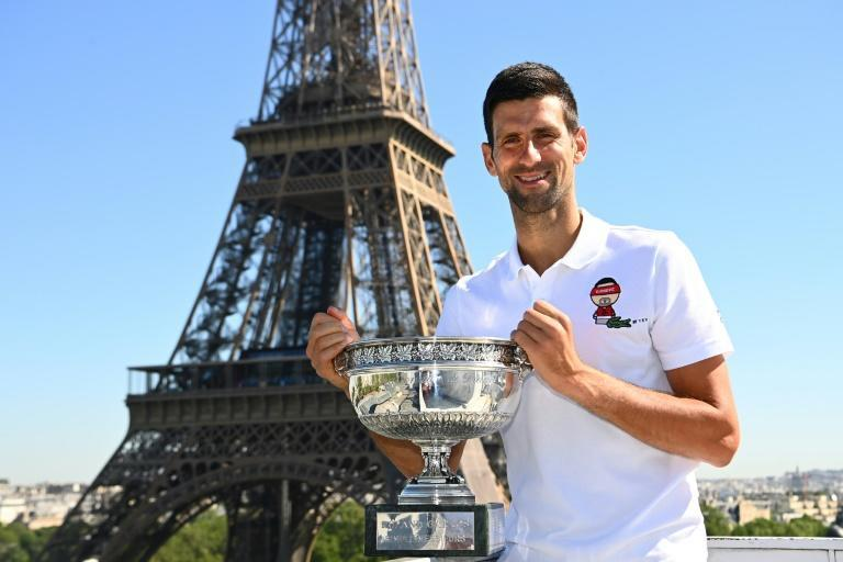 Tower of strength: Novak Djokovic poses with the French Open trophy in front of the Eiffel Tower on Monday