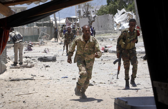 Somali government soldiers run to take positions during ongoing fighting with gunmen after a suicide car bomb attack on a government building in the capital Mogadishu, Somalia Saturday, March 23, 2019. Al-Shabab gunmen stormed into the government building following a suicide car bombing at the gates on Saturday, a police officer said, in the latest attack by Islamic extremist fighters in the Horn of Africa nation. (AP Photo/Farah Abdi Warsameh)