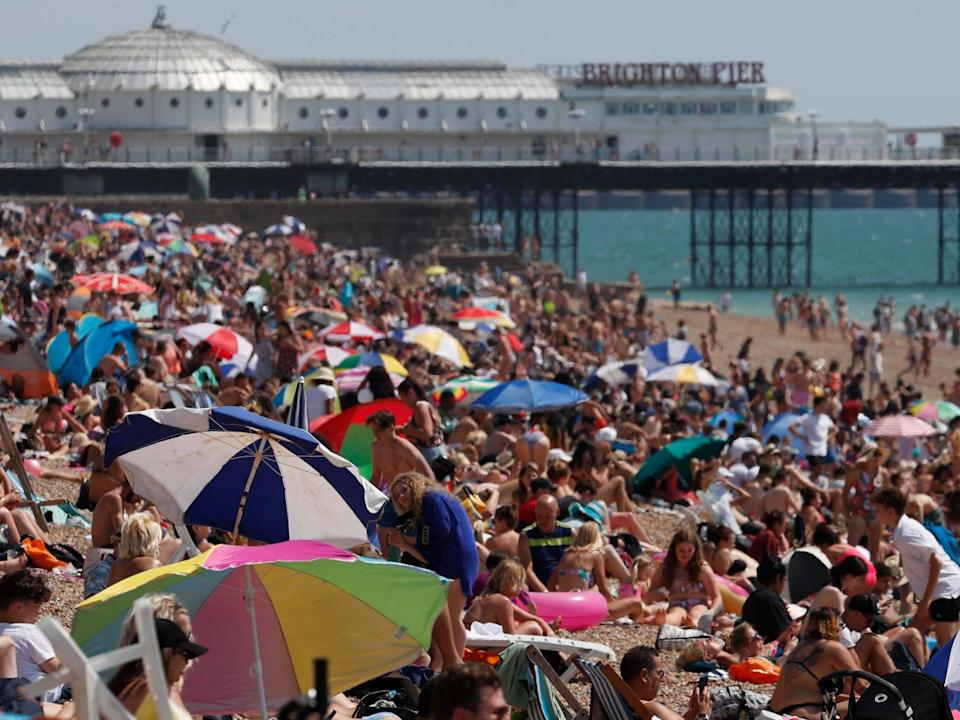 Beachgoers enjoy the sunshine and sea on what is now Britain's hottest day of the year so far, in Brighton, Friday 31 July: AP