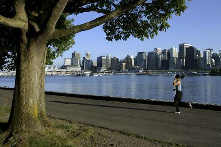 FILE PHOTO: A jogger runs along the seawall in Stanley Park with the city skyline in the background