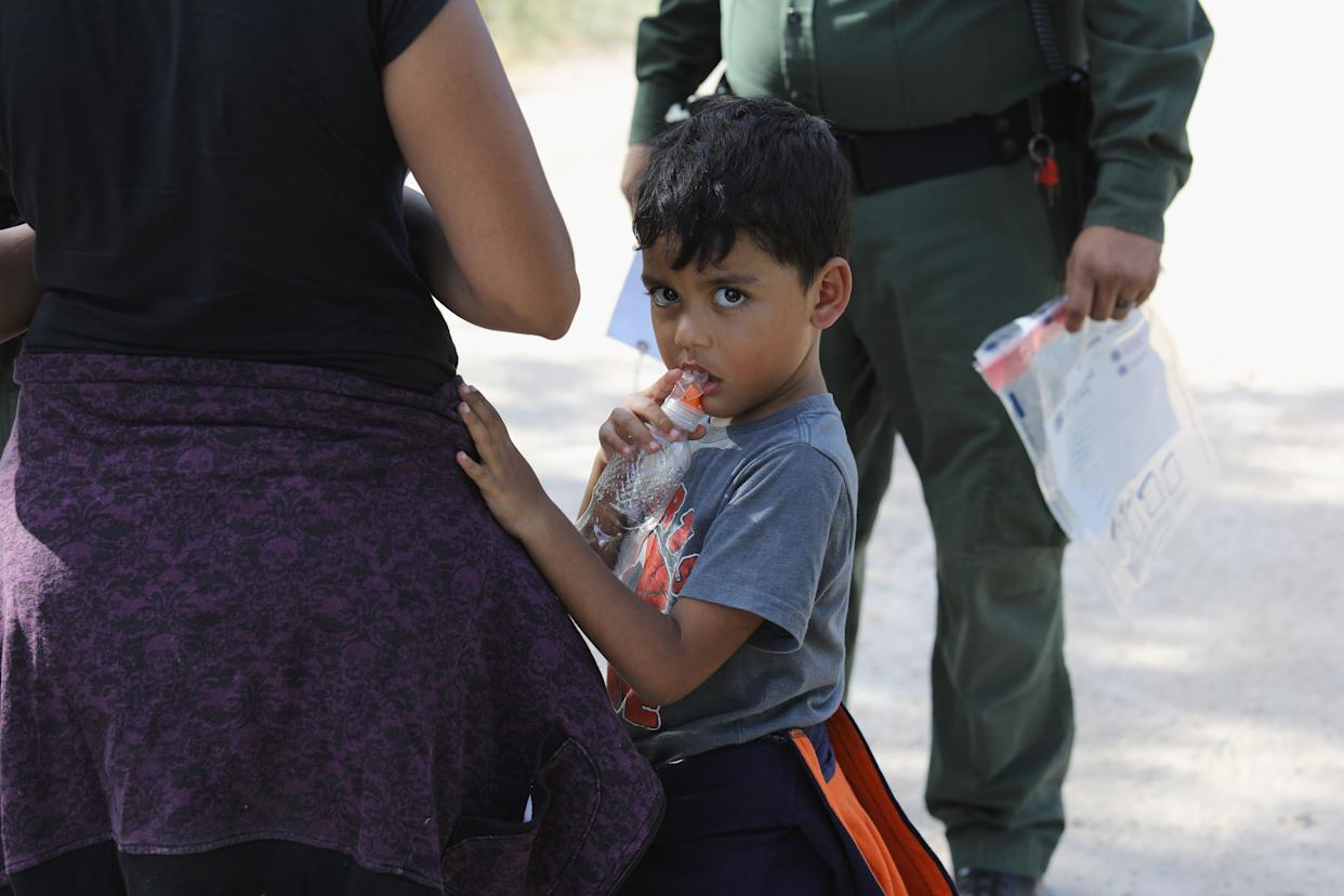 Central Americans seeking asylum wait as U.S. Border Patrol agents take them into custody on June 12, 2018, near McAllen, Texas.
