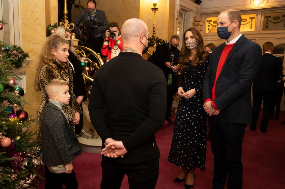Wearing protective face coverings to combat the spread of the coronavirus, Britain's Prince William, Duke of Cambridge (R) and Britain's Catherine, Duchess of Cambridge (2nd R) speak with guests at a special pantomime performance of The National Lotterys Pantoland  at London's Palladium Theatre in London on December 11, 2020, to thank key workers and their families for their efforts throughout the pandemic. (Photo by Aaron Chown / POOL / AFP) (Photo by AARON CHOWN/POOL/AFP via Getty Images)