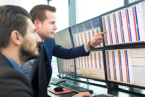 Businessmen looking at array of monitors with stock data.