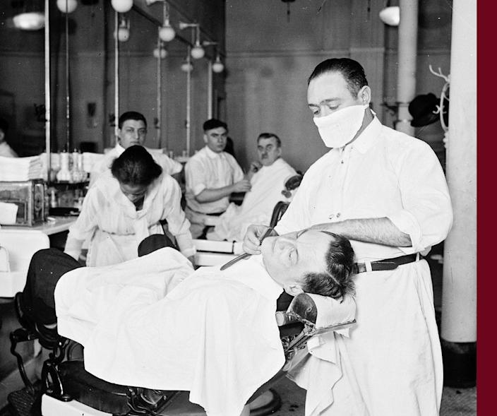 A barber in a barbershop shaving a man's face wears a mask to protect against influenza in Chicago in 1918.
