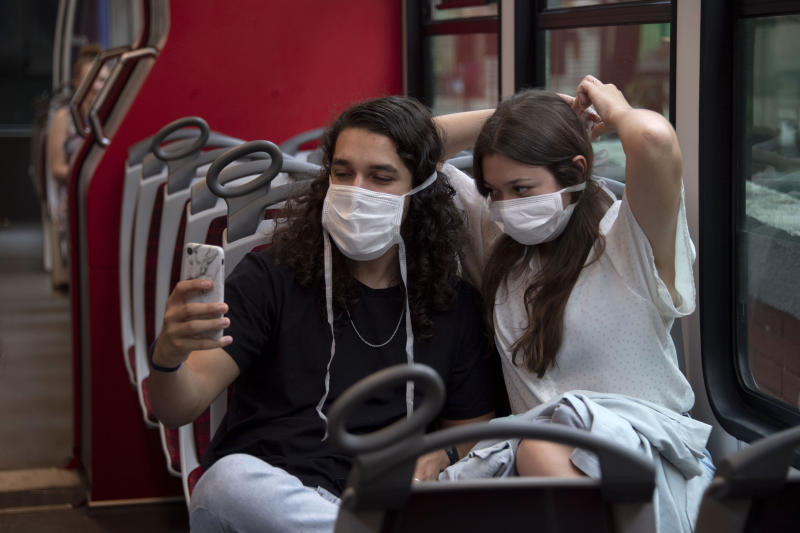 Tourists make a selfie wearing face masks onboard the Corcovado hill train, on their way up to see the statue of Christ the Redeemer in Rio de Janeiro, Brazil, on March 17, 2020. - Rio de Janeiro's state government closed the iconic Christ the Redeemer statue and the cable car to Sugarloaf Mountain, two of the city's most famous attractions, as an emergency measure to stop the spread of the new coronavirus COVID-19. (Photo by MAURO PIMENTEL / AFP) (Photo by MAURO PIMENTEL/AFP via Getty Images)