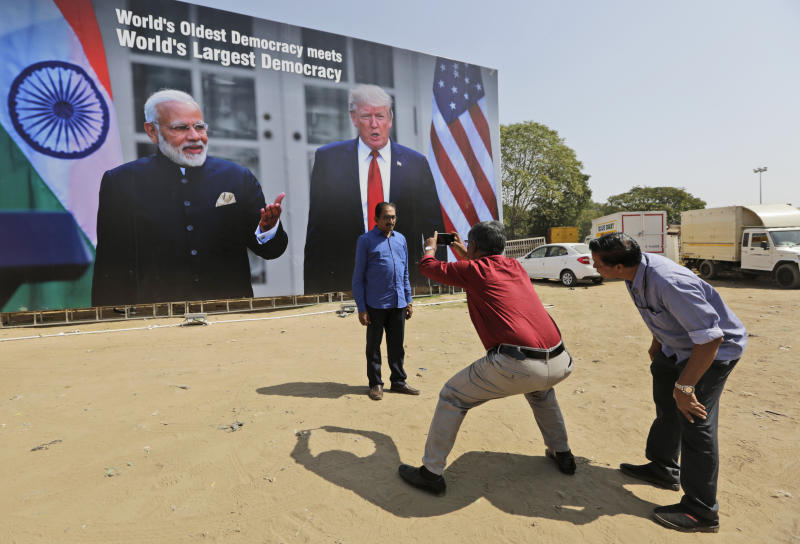 A man stands for a photograph in front of a hoarding welcoming U.S President Donald Trump, at the airport ahead of his visit in Ahmedabad, India, Saturday, Feb. 22, 2020. To welcome Trump, who last year likened Modi to Elvis Presley for his crowd-pulling power at a joint rally the two leaders held in Houston, the Gujarat government has spent almost $14 million on ads blanketing the city that show them holding up their hands, flanked by the Indian and U.S. flags. (AP Photo/Ajit Solanki)