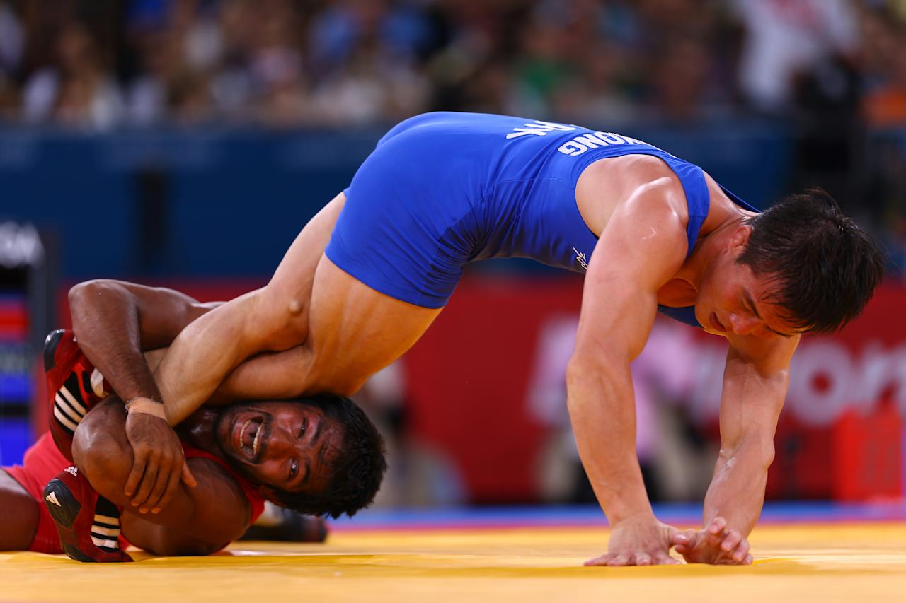 LONDON, ENGLAND - AUGUST 11:  Yogeshwar Dutt of India (red) and Jong Myong Ri of DPR Korea compete in the Men's Freestyle 60 kg Wrestling on Day 15 of the London 2012 Olympic Games at ExCeL on August 11, 2012 in London, England.  (Photo by Paul Gilham/Getty Images)