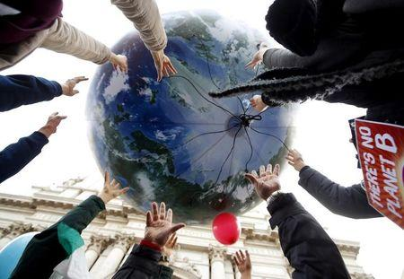 FILE PHOTO: Protesters throw up a globe-shaped balloon the day before the start of the 2015 Paris World Climate Change Conference
