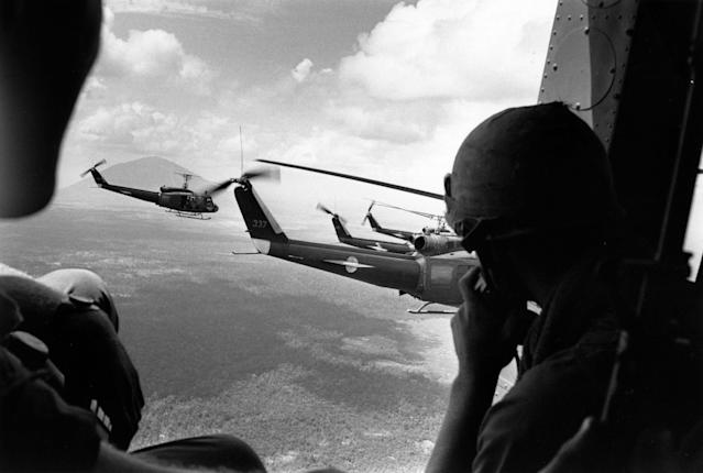 <p>A crewman in a US helicopter watches a group of escorting Bell Huey helicopters during an operation in the Vietnam War. (Photo: Terry Fincher/Daily Express/Hulton Archive/Getty Images) </p>