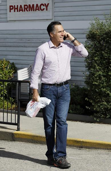 Republican presidential candidate, former Massachusetts Gov. Mitt Romney talks on the phone as he walks out of a pharmacy in Wolfeboro, N.H., Monday, Aug. 6, 2012. (AP Photo/Charles Dharapak)
